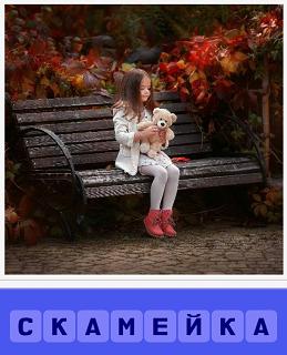 на скамейке сидит девочка и играет с плюшевым медведем