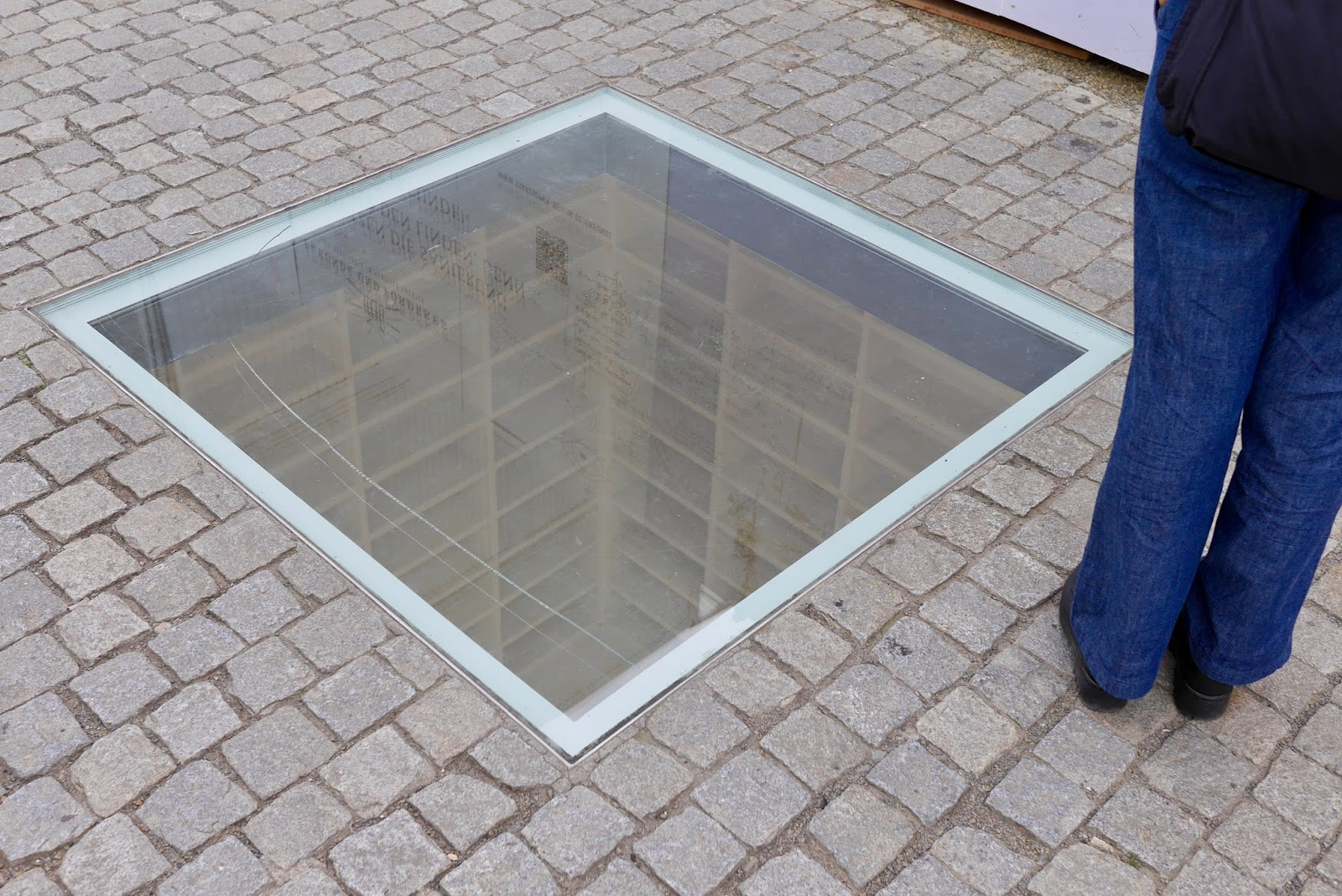 A subtle window in the middle of a square in berlin showing empty bookshelf to depict the burning of all books created by the jewish
