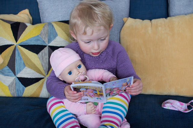 A toddler reading to Baby Annabell