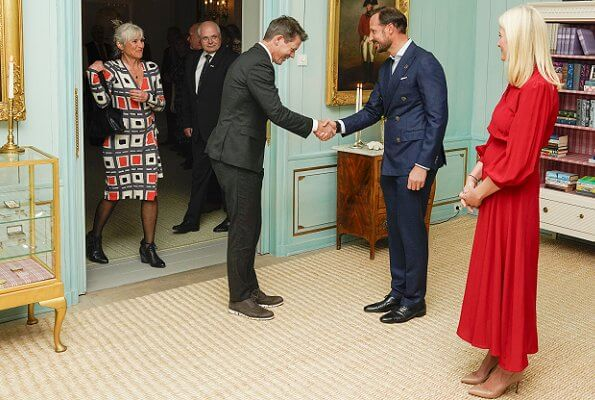 Norwegian Crown Couple host a traditional banquet for representatives of the civil society. red silk blouse and red skirt