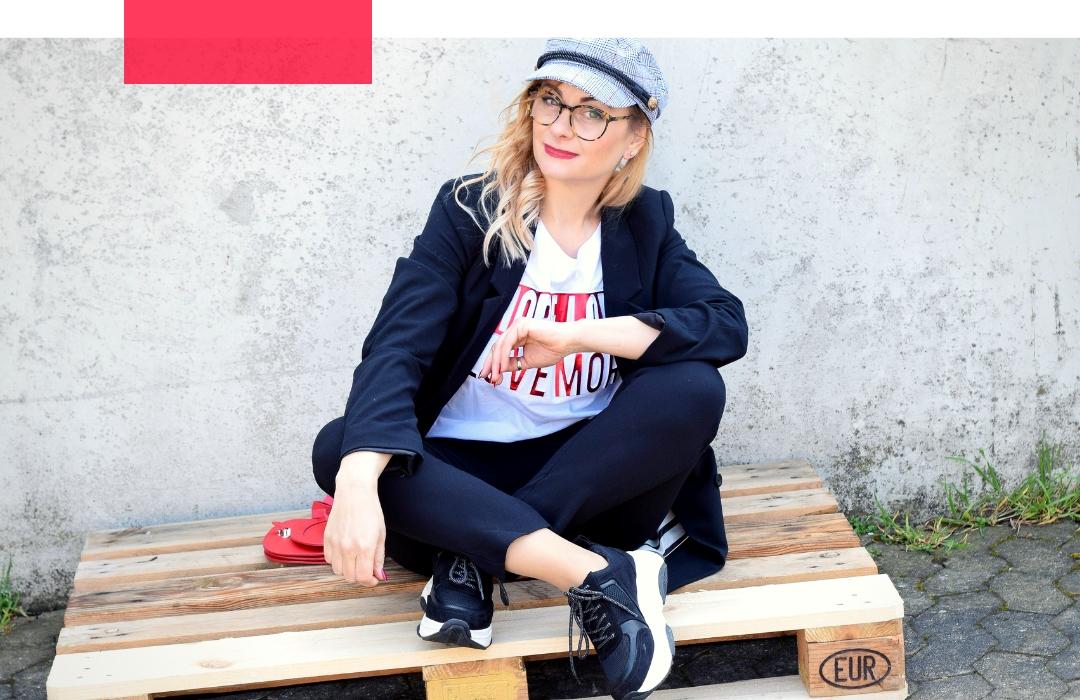 Frau im schwarzen Business Anzug, T-Shirt und Chunky Sneakern