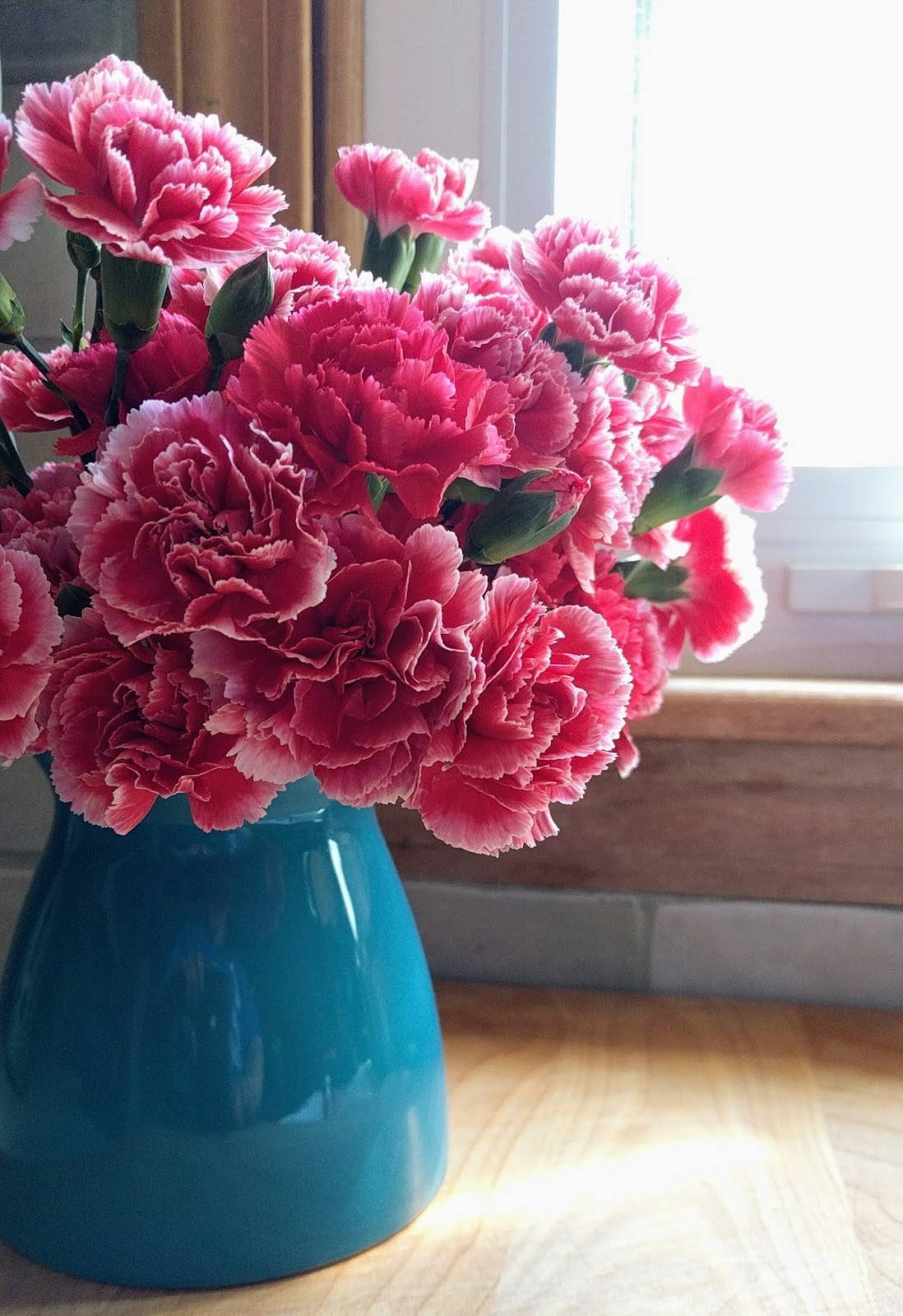 Deep pink carnations in a turquoise blue ceramic vase