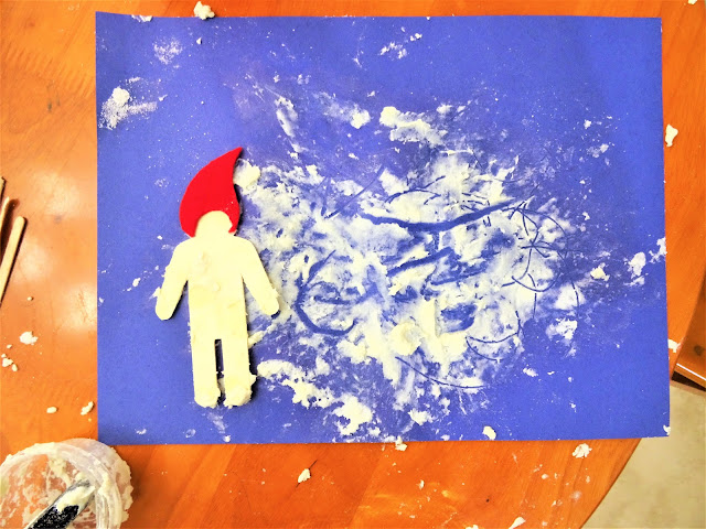 Blue cardstock paper with a small wooden effigy of a boy with a red cap. What appears to be snow on the cardstock paper. A small plastic container on the bottom left with snow residue.