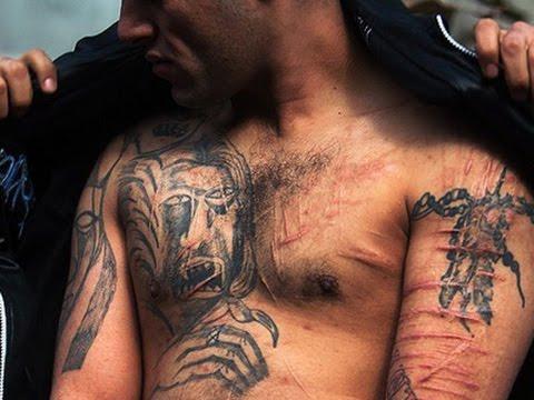 Imagen de un hombre cubriendo a otro con chaqueta Tapando tatuajes por estra prohibidos