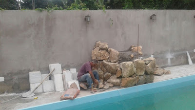 Bizzarri fazendo uma cascata de pedra na piscina com pedras ornamentais tipo pedra moledo bege.