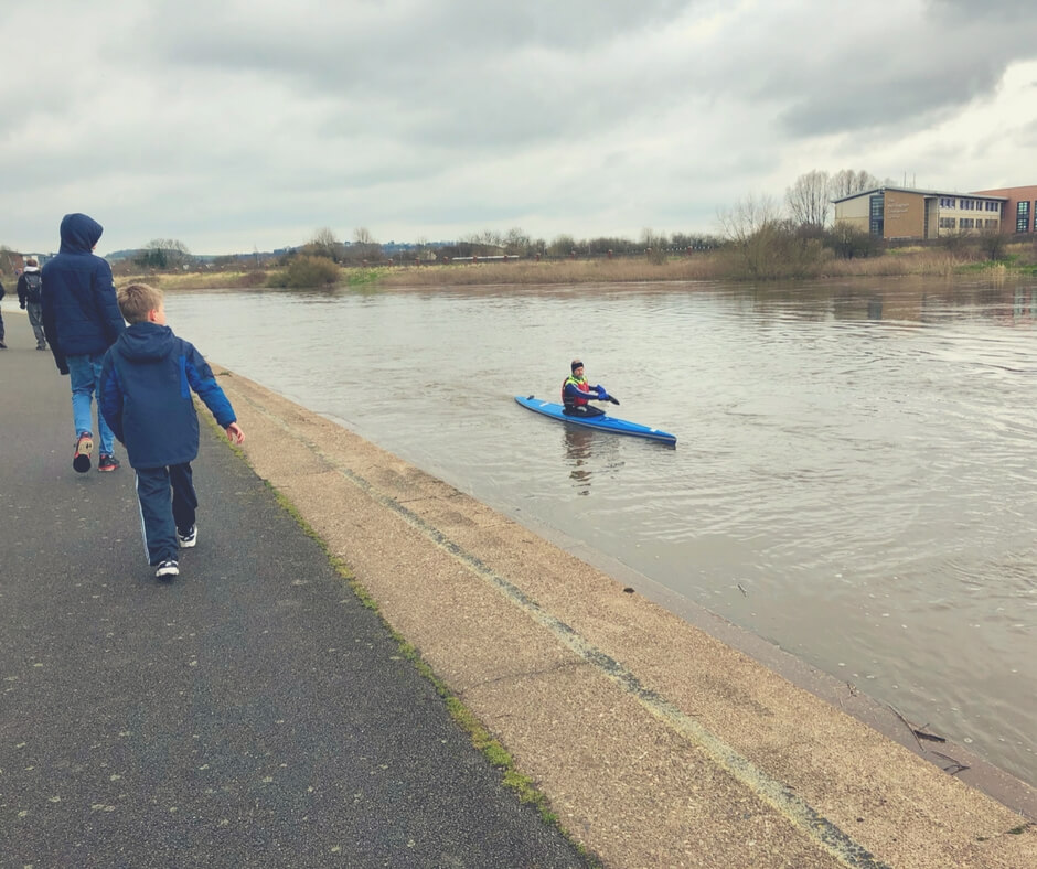 Two boys walk along the path alongside the River Trent, they are both looking at a rower who is rowing his canoe up the river. Image for Easter lunch at Barburrito Nottingham (and Giveaway!).