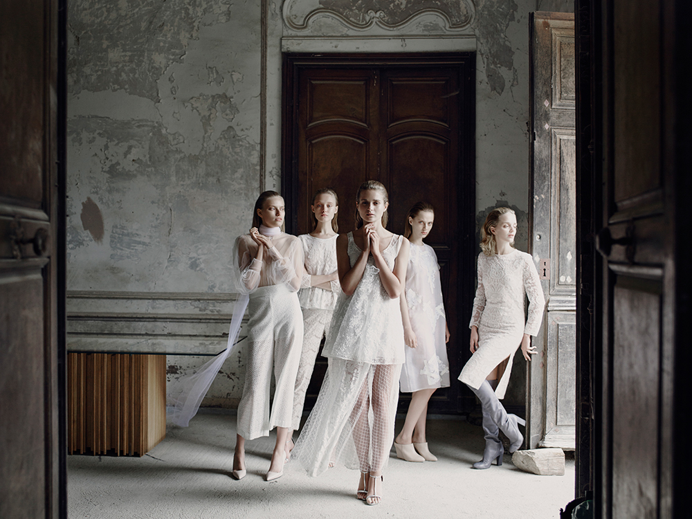 Models in white in peeling wallpaper decaying French Chateau Gudanes