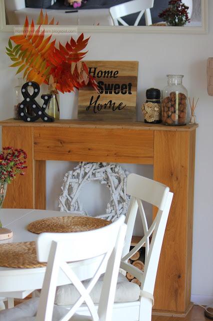 bukiet z liści, liście w ramce, jesień w salonie, biały salon, drewniana ściana w salonie,  stolik Isala, Atrapa kominka DIY, biały stół Ingatorp Ikea, białe krzesła Ingolf