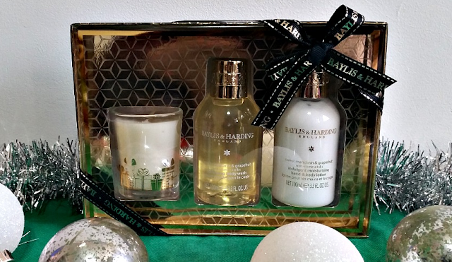 Sweet Mandarin & Grapefruit Festive Trio of Treats gift box surrounded by silver tinsle and baubles