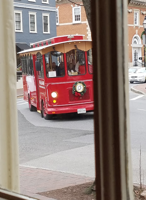 red tourist bus with wreath on the front at church circle