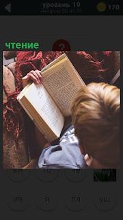 Молодой человек в кресле с книгой занимается чтением интересного романа