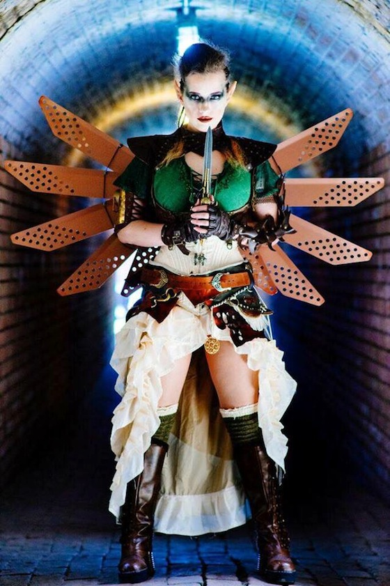 Woman in steampunk fairy costume with wings, knife, skirt, corset, boots, armor, steampunk makeup