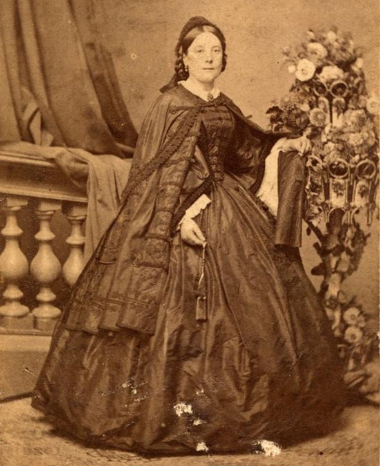 91a9a3e76e 1860 körüli elegáns asszony a ruhával összhangzó gazdagon díszített selyem  mentében, a ruha dereka alapszabású, annak is magyaros jelleget a  zsinórozás ad.