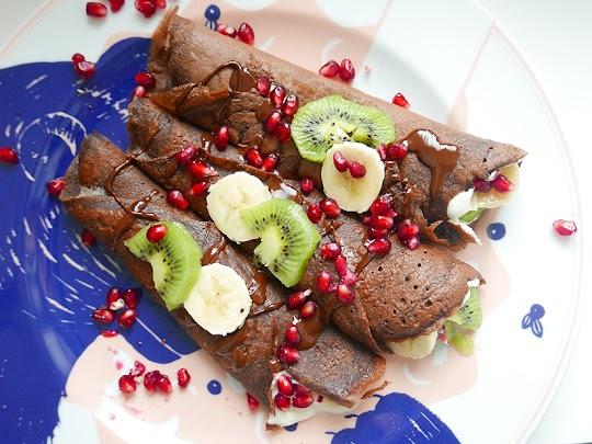 Orkiszowe, czekoladowe naleśniki z bitą śmietaną, kiwi, bananami, ziarnami granatu i rozpuszczoną czekoladą