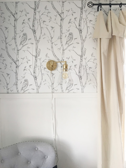 gray and white woodland wallpaper with gold sconces