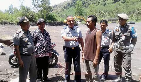 Petugas menghalau kendaraan berat yang akan masuk ke lokasi tambang tak berizin