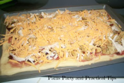 Adding the cheese on top of the leftover turkey pizza