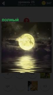 В ночное время полный диск луны склоняется за горизонт над водой
