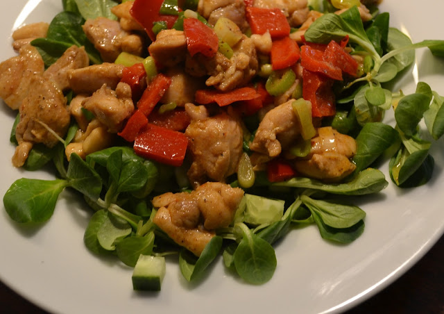 salade van veldsla met stukjes kruidige kip en paprika op een bord