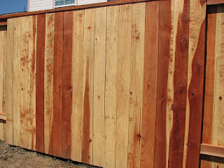 Photo of a new redwood fence showing color variations.