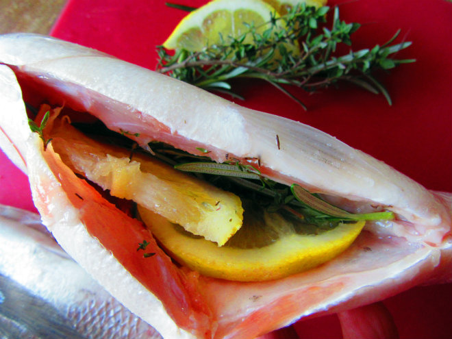 Gilt-head bream with romesco sauce by Laka kuharica: stuff the inside of the fish with lemon slices and herbs.
