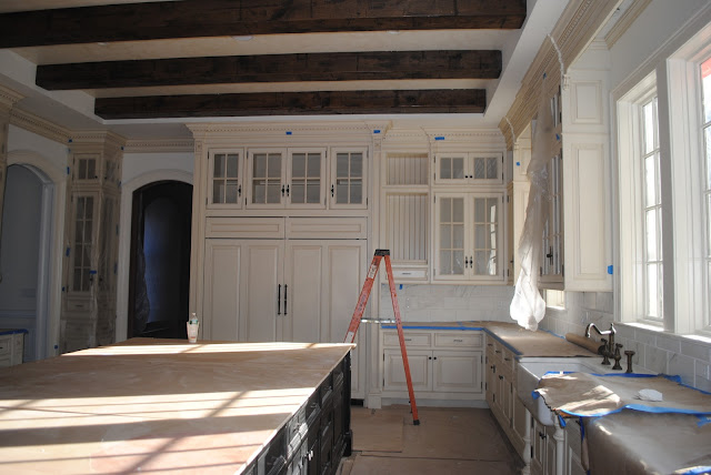 Under construction French Country kitchen with white cabinets, wood beams, and farm sink