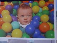 baby in ball pit with bright coloured balls