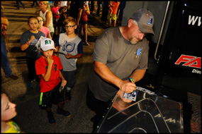 Scott Treadway signs autographs for several young fans at a Bandit Big Rig Series event at Hawkeye Downs Speedway on Saturday, July 15, 2017