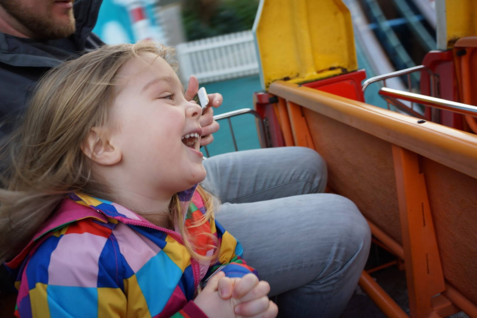 toddler laughing on a fairground ride