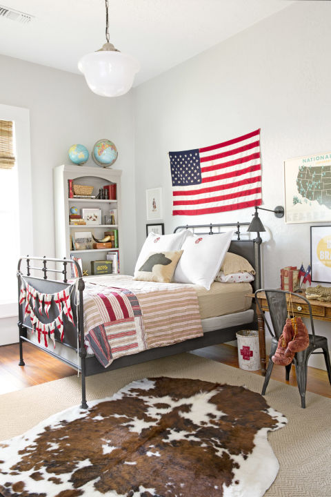 Patriotic bedroom decor in a boys room of charming cottage in Texas with interior design by Holly Mathis. American flag ung over vintage bed, cowhide rug, and French cafe chair work magic in the farmhouse style mix. #bedroom #patriotic #farmhousestyle #cottage #decorating #americana