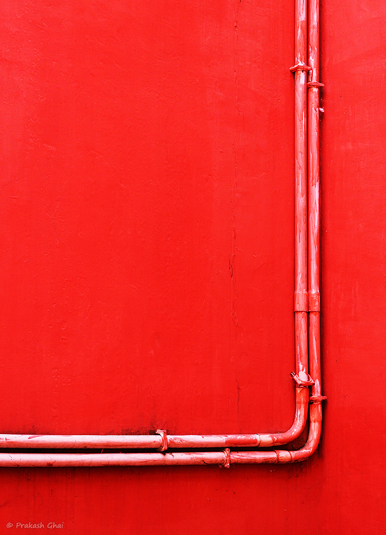 A Minimalist Photo of Two pipes in close proximity or in love, against a red wall