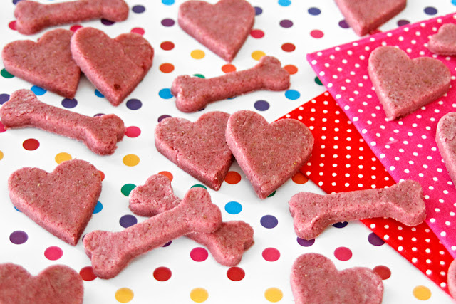 Pink heart and bone shaped Valentine's Day dog treats on a polka dot background