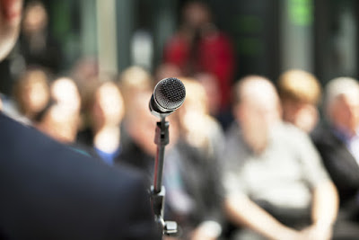 A microphone awaits you in front of a large audience