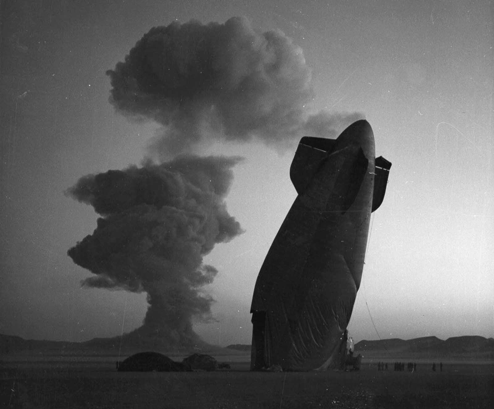At a Nevada nuclear test site test Site, on August 7, 1957, the tail of a U.S. Navy Blimp is photographed with the cloud of a nuclear blast in the background. The Blimp was in temporary free flight in excess of five miles from ground zero when it collapsed from the shock wave of the blast. The airship was unmanned and was used in military effects experiments. Navy personnel on the ground in the vicinity of the experimental area were unhurt.