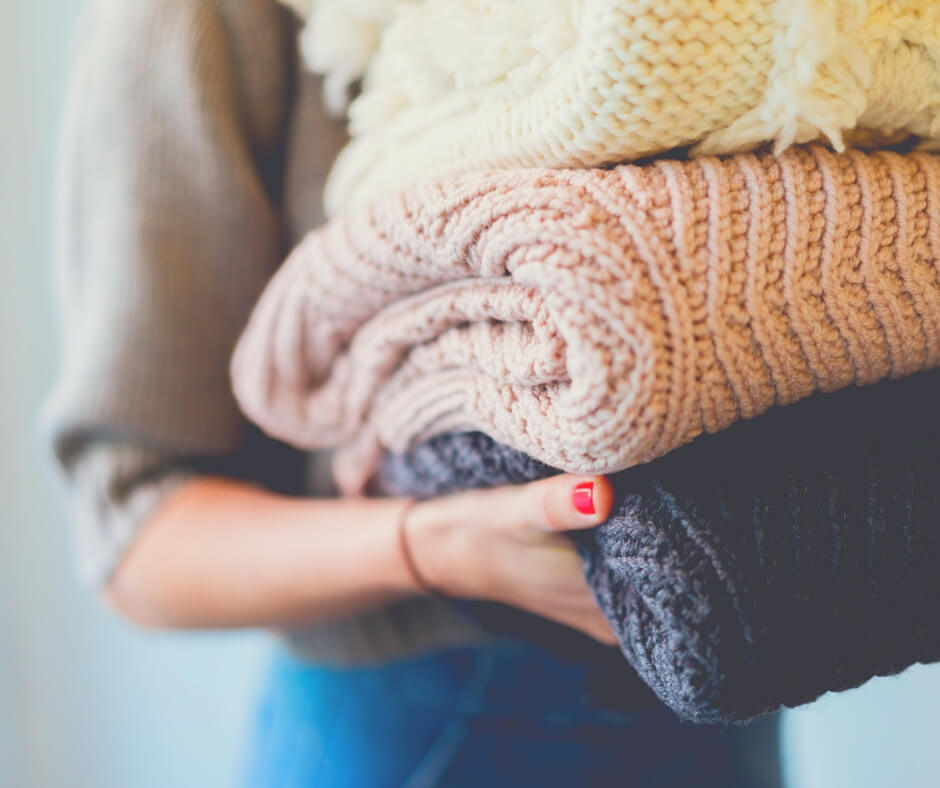 Post Comment Love 26th - 28th October | woman holding a pile of folded wool sweaters.