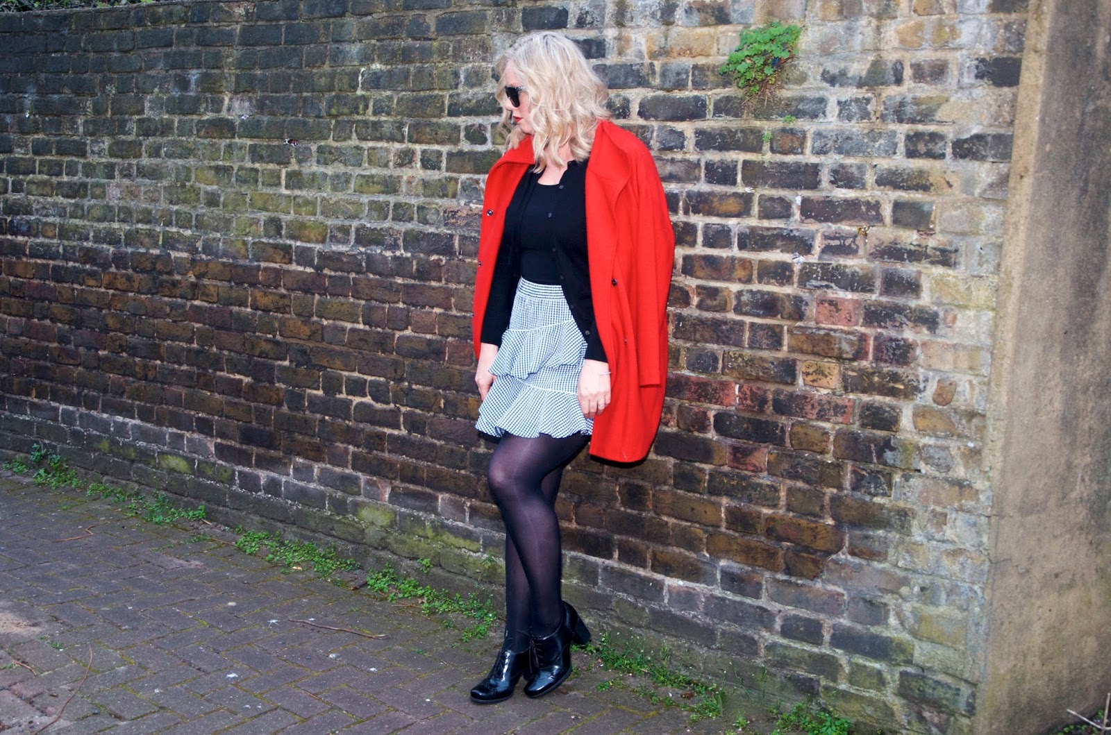 leaning on a brick wall with a red coat