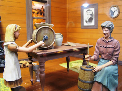 Model of a 19th-century woman and child inside a house, churning butter.