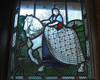 Stained glass window depicting a woman in medieval dress on a white horse, Mabie House, Mabie Forest, Scotland