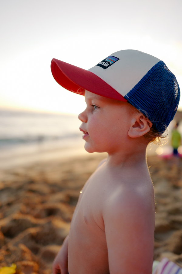 Toddler taking in the sunset at Poipu Beach, Kiahuna Plantation (+ fave Patagonia hat)