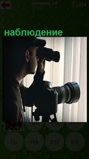 ведется наблюдение через окно с помощью бинокля и стоит фотоаппарат