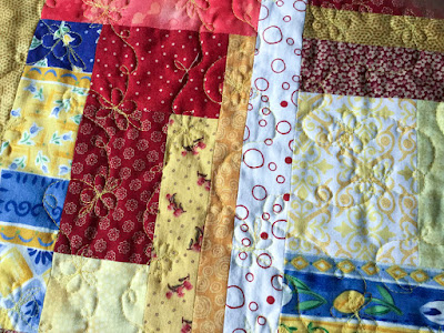 Free motion quilting in yellow on the scrappy side of the placemat