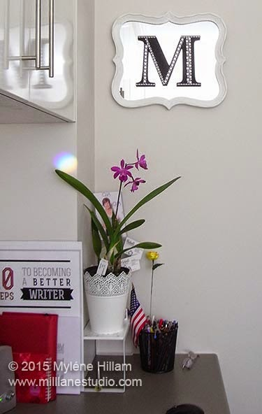 "Office corner decorated with purple orchid and DIY decorative mirror with white frame and ""M"" painted black and decorated with crystal and pearl borders."