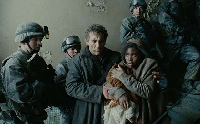 A man escorts a woman with her newborn as the combatants stop fighting, awed by the miracle, in Children of Men, Clive Owen