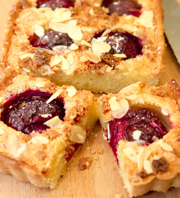 A slice of plum frangipane tart with flaked almonds and crushed amaretti