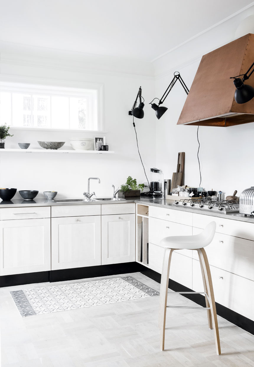 White kitchen inside of Scandinavian villa, black decor, copper hood