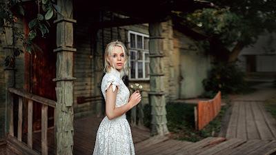 Linda chica de rubia vestida de blanco mirando a cámara con flores en la mano