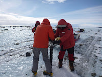 Team Members Taking a Short Ice Core to Study Properties of Sediment Coming from the East Antarctic Ice Sheet. (Image Credit: Lamont-Doherty Earth Observatory) Click to Enlarge.