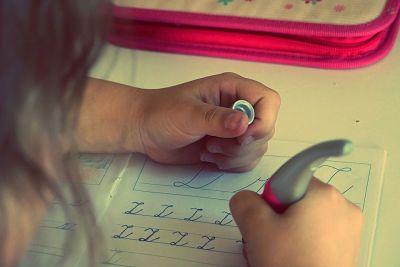 Deberes de los niños. Mano de niña escribiendo letras en una hoja.
