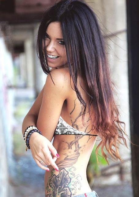 Chica miorena de perfil, lleva ttuajes de flores, y tatuaje de arbol que le sube por el costado