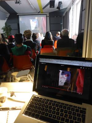 Publikum von hinten, Leinwand und Laptop mit Film